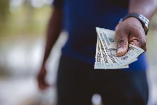 Closeup shot of a person holding three twenty dollar bills with a blurred background