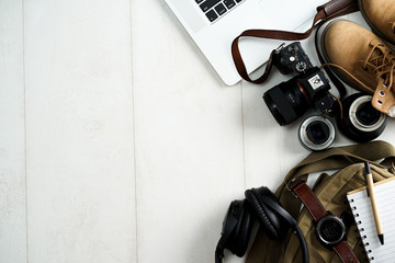 Camping or adventure trip scenery concept. Backpack, boots, belt, thermos and camera on wooden background captured from above (flat lay). Layout with free text (copy) space.