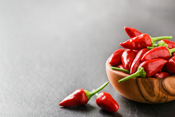 Fototapeta Hot pepper in wooden bowl on dark stone table. Chili red peppers and green leaves on black background. obraz