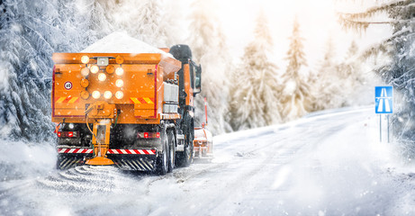 Salting highway maintenance. Snow plow truck on snowy road in action. Hard weather condition in winter. Vehicle spreading deicing salt.