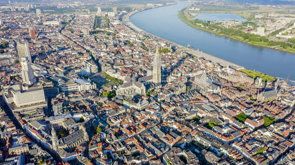 Zelfklevend Fotobehang Antwerpen Antwerp, Belgium. Flying over the roofs of the historic city. Schelde (Esco) river. Cathedral of Our Lady of Antwerp. (Onze-Lieve-Vrouwekathedraal Antwerpen), Aerial View