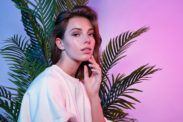 Fototapeta Beautiful female touching face with tenderness. Lady sitting near green palm tree and looking at camera with tenderness. Beauty and fashion concept obraz