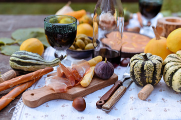 Autumn picnic in the park. Pumpkins, pie, prosciutto and snacks. Bottle of wine and glasses on a wooden table. Sunny day and outdoor recreation.