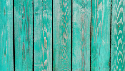 Texture of weathered wooden green painted fence