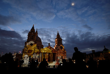 People view and record light projections depicting Second World War images seen on the west face of St Paul's Cathedral as part of the forthcoming 'Where Light Falls' illuminations and poetry readings, in London, Britain
