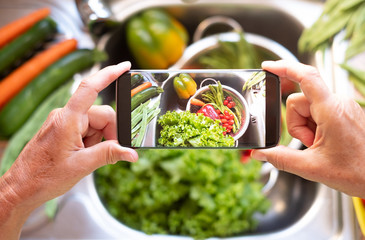 A lady's hands take a picture with her cell phone to clean vegetables. Healthy food to stay in shape and for vegan and vegetarian people