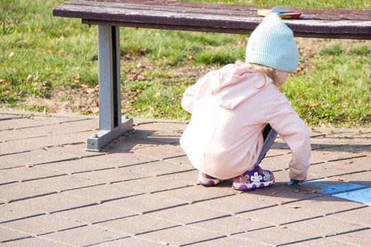 Little girl draws with chalk. The park. Autumn.