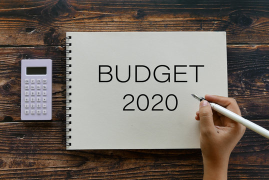Top view of calculator and hand holding pen writing Budget 2020 on notebook on wooden background.