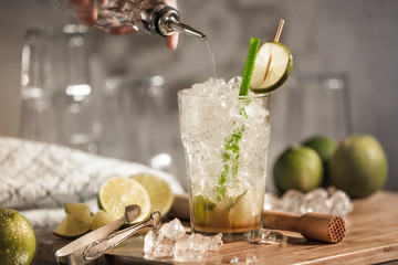 A glass of caipirinha on a wooden board with limes and crushed ice as decoration. A fresh traditional Brazilian cocktail with citrus fruits and rum.