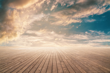 Empty wooden floor against cloudy sky with sunset.