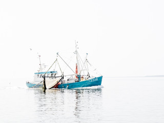 High key image of shrimp fishing trawler off coast Vlieland on Waddensea, Netherlands