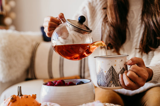 woman having a cup of tea at home during breakfast. Cute golden retriever dog besides. Healthy breakfast with fruits and sweets. lifestyle indoors
