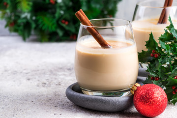 New Year or Christmas Eggnog cocktail with cinnamon and nutmeg in a glass, branches of holly berries and ball toy on light stone background, festive decoration Fototapete
