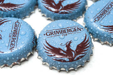 Mulhouse - France - 23 October 2019 - Closeup of drops on blue Grimbergen bier caps on white background