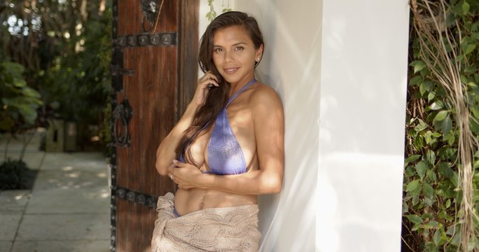 Smiling charming woman in swimwear leaning against wall