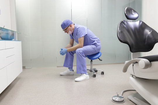 Tired middle age, male dentist in his office sitting on stool, having break,waiting for patient in his office
