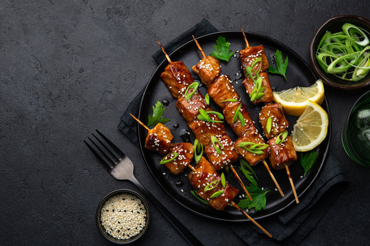 Teriyaki salmon skewers on black plate