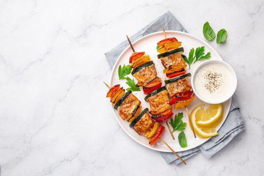 Grilled salmon and vegetables skewers on white plate