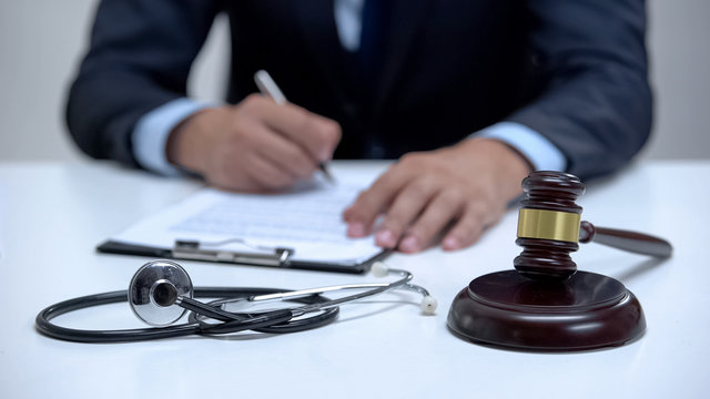 Judge signing arrest warrant for medical error, banging gavel near stethoscope