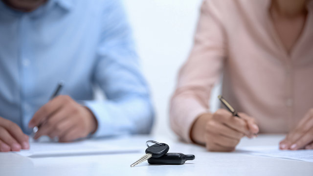 Car keys closeup, couple signing divorce documents about property division