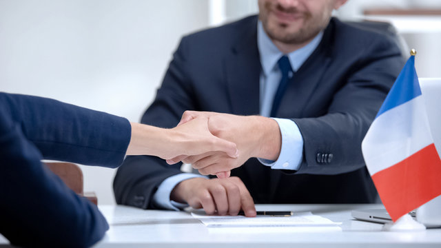 French official signing docs about state business support, shaking partner hand
