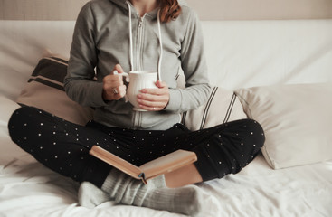 girl in home clothes on the couch reads a book and drinks a hot drink