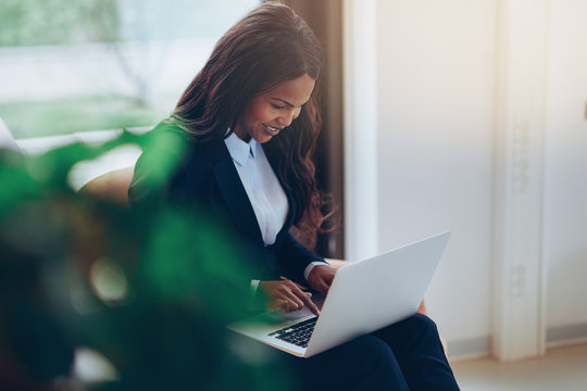 Smiling African American businesswoman using a laptop in an offi