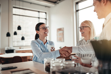Smiling businesspeople shaking hands together during their coffe