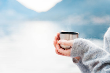 Woman with mug of coffee by winter sea, blue mountains. Cozy picnic with thermos of hot steamy beverage tea or mulled wine on beach. Girl is enjoying nature, life, relaxation, Christmas mood.