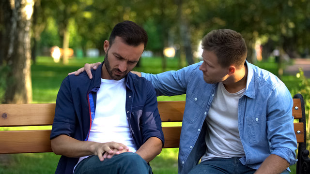 Young male supporting friend sitting outdoors together, friendship care, advice