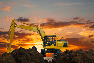 Excavators are digging the soil in the construction site on the sunset background