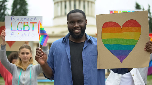 Black man with rainbow symbols amid protesters for LGBT rights, pride events
