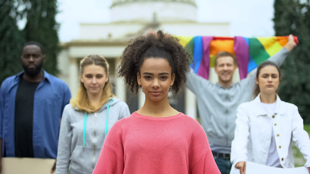 Activists protesting against discrimination holding rainbow flag, LGBT community