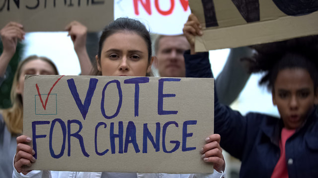 Sad girl showing slogan Vote for change, presidential campaign rally, democracy
