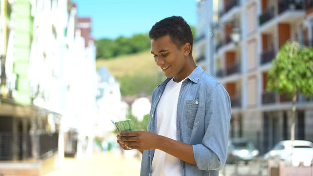 Joyful afro-american teen male counting euros, happy to go shopping, income
