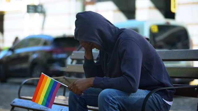 Black man in hood sitting on bench with lgbt minority flag, preconceptions