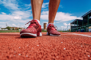 men's feet in red sneakers at the sports stadium. shooting from a lower angle