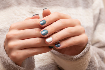 Female hands with blue glitter nail design.