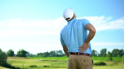 Athletic man golfer suffering sharp lower back pain, sport trauma, health