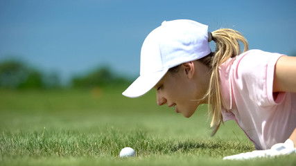 Female golf player looking at ball rolling in hole, hope for success shot, sport