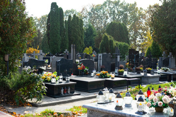 Graves at a Christian cemetery in autumn. All Saints Day. Tombstones decorated with flowers and grave candles. Fototapete