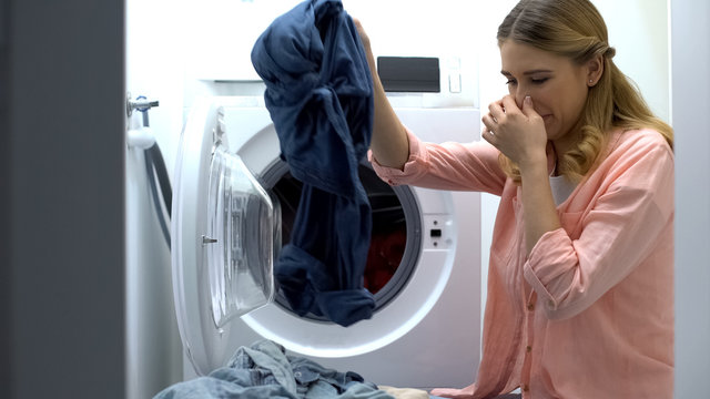 Woman closing nose from stinky clothes after washing, low-quality soap-powder