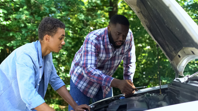 American father explaining car structure to son showing auto parts, togetherness