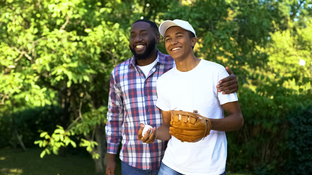 Happy father praising son playing baseball in park, family support, connection