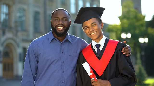 Proud glad father hugging graduating son with diploma, education degree, success