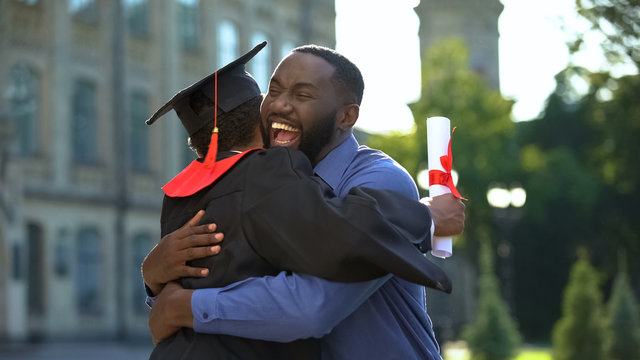 Cheerful father and graduating son hugging outdoor, study achievement, education