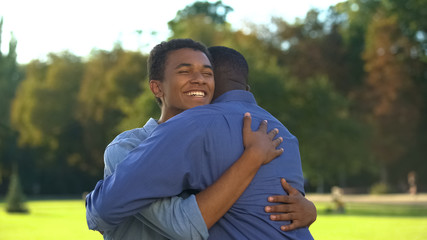 Fototapeta Male teenager hugging elder brother outdoors, family meeting happiness, love obraz