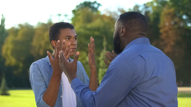 American father and teenage son arguing outdoors, family conflict, communication