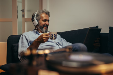 man listening music on headphones in his home