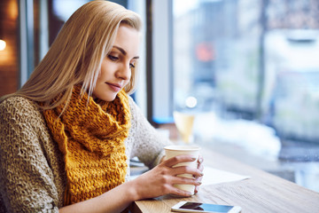 Beautiful young woman warming up in cafe during cold winter day.